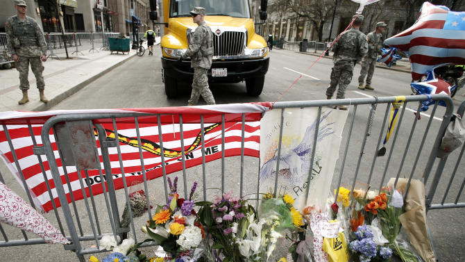 Flowers are placed by a Boston police barricade near the finish line of the Boston Marathon in Boston, Tuesday, April 16, 2013. The bombs that ripped through the crowd at the Boston Marathon, killing three people and wounding more than 170, were fashioned out of pressure cookers and packed with metal shards, nails and ball bearings to inflict maximum carnage, a person briefed on the investigation said Tuesday. (AP Photo/Winslow Townson)