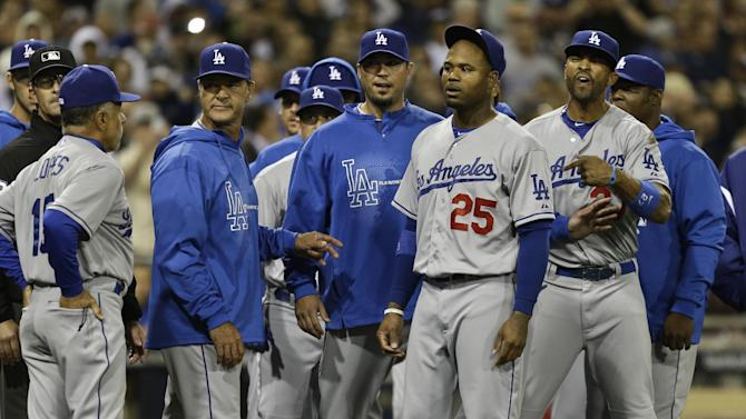 Los Angeles Dodgers' Carl Crawford, (#25), Matt Kemp, right, Josh Beckett, third from left, and manager Don Mattingly, fourth from left, stand in front of the San Diego Padres dugout in a confrontation following a braw during the eighth inning of baseball game in San Diego, Thursday, April 11, 2013. The braw started when San Diego Padres' Carlos Quentin was hit by a pitch from Dodgers pitcher Zack Greinke.  (AP Photo/Lenny Ignelzi)