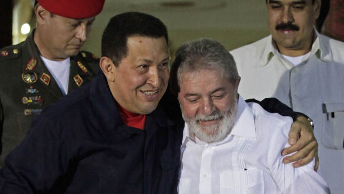 FILE - In this July 2, 2001 file photo, Venezuela's President Hugo Chavez, left, welcomes Brazil's former President Luiz Inacio Lula da Silva at Miraflores presidential palace in Caracas, Venezuela. After four election wins, Chavez is on track to completing at least 20 years in power.  Some critics are uneasy about the health of democracy in a region where a single person can remain in office for a generation. Even Chavez's friend and ally, Lula, publicly advised the Venezuelan leader that a fourth term ought to be enough. (AP Photo/Ariana Cubillos, File)