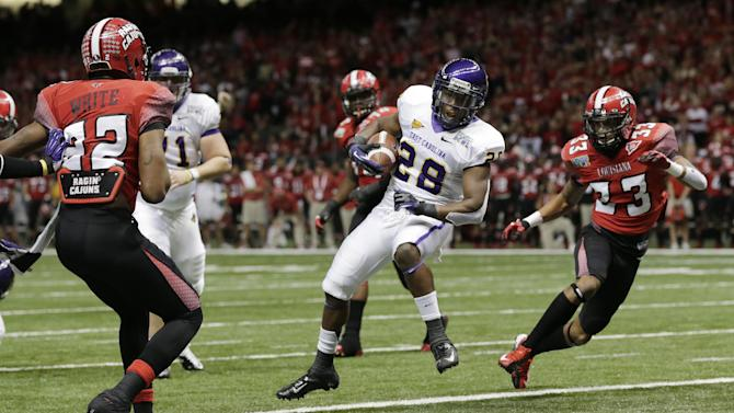 East Carolina running back Reggie Bullock (28) scores a touchdown as Louisiana-Lafayette safety Trevence Patt (33) and Louisiana-Lafayette cornerback Melvin White (22) defend in the first half of the New Orleans Bowl, an NCAA college football game in New Orleans, Saturday, Dec. 22, 2012. (AP Photo/Dave Martin)