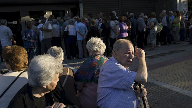 People queue to receive their pensions in front of a National Bank in Athens