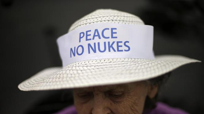 Lyn Harris Hicks, a longtime opponent of the San Onofre nuclear power plant and a nearby resident, wears a banner on her hat as she waits for a news conference in front of the plant Friday, June 7, 2013, in San Onofre, Calif. The troubled power plant on the California coast is closing after an epic 16-month battle over whether the twin reactors could be safely restarted with millions of people living nearby, officials announced Friday. (AP Photo/Gregory Bull)