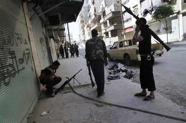 In this Wednesday, Aug. 1, 2012 photo, Free Syrian Army soldiers are seen during clashes with government forces at the south-west district of Salah al-Din in Aleppo, Syria. Syrian troops launched a ground assault Wednesday on the besieged northern city of Aleppo, but activists said rebels forces were fighting back in a battle for the country's largest city that has raged for more than two weeks. (AP Photo/Alberto Prieto)