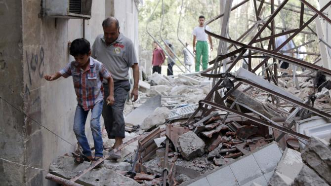 Residents walk over rubble after what activists said were barrel bombs thrown by forces of Syria's President Bashar al-Assad in Zebediah neighbourhood of Aleppo city