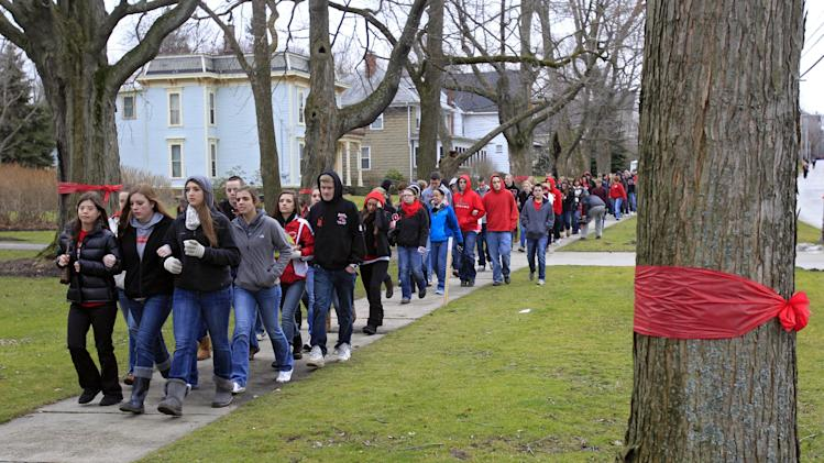 Students and parents march to the high school in Chardon, Ohio Thursday, March 1, 2012, to honor the three students who were killed in a shooting there Monday. The school re-opened to parents and students Thursday and classes resume Friday. (AP Photo/Mark Duncan)