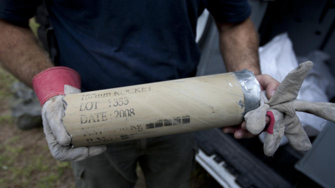 An Israeli police sapper holds the remains of a rocket rocket fired by Palestinian militants after it hit a community along the Israel Gaza Border, southern Israel, Wednesday, Oct. 24, 2012. Rockets and mortars from Gaza have pummeled southern Israel, drawing Israeli airstrikes that killed a Palestinian militant. The Israeli military said 60 rockets and mortars were fired early morning Wednesday, following a volley the night before and that Israeli aircraft struck Gaza three times. (AP Photo/Ariel Schalit)