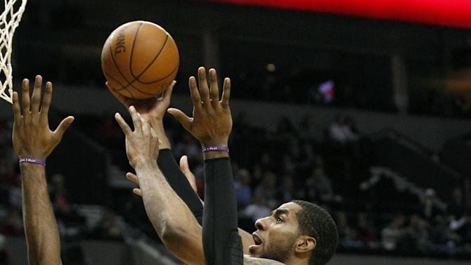 Portland Trail Blazers' LaMarcus Aldridge, center, goes to the basket as Sacramento Kings' Jason Thompson (34) and teammate DeMarcus Cousins (15) defend in the third quarter during an NBA basketball game Monday, Jan. 23, 2012, in Portland, Ore. The Trail Blazers defeated the Kings 101-89. (AP Photo/Rick Bowmer)