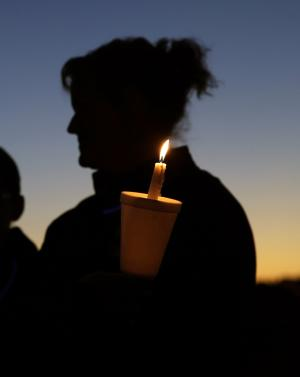 A person holds a candle as they join others at an anti-bullying …