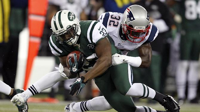 New York Jets running back Shonn Greene (23) is tackled by New England Patriots cornerback Devin McCourty (32) during the first half of an NFL football game on Thursday, Nov. 22, 2012, in East Rutherford, N.J. (AP Photo/Julio Cortez)