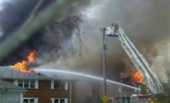 Firefighters douse an apartment complex in the tourist resort of Virginia Beach, Virginia, where a US Navy F-18 jet fighter crashed after take-off April 6, 2012. Firefighters combed through the debris of the complex Saturday after the crash, which caused a massive inferno but injured only nine people