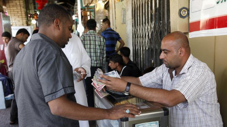 A man exchanges money at a street money changers in Karbala, 50 miles (80 kilometers) south of Baghdad, Iraq, Sunday, June 23, 2013. Citigroup Inc. is set to become the first American bank to open an office under its own name in Baghdad, highlighting international financial firms' growing interest in Iraq a decade after the U.S.-led invasion. (AP Photo/ Hadi Mizban)