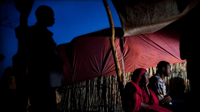 Refugees from South Kordofan, Sudan, gather around a small TV set in  the Yida refugee camp in Unity State, South Sudan on Saturday May 12, 2012. What little electricity exists in the camp comes from small generators and fuel is in short supply. More than 30,000 refugees currently reside in Yida having fled war between the government of the Republic of Sudan and rebel forces in South Kordofan. In recent weeks, aid agencies have reported a steep influx of new arrivals, at times exceeding 700 per day. Most arrive in need of food, medical treatment and other basic services. (AP Photo/Pete Muller)