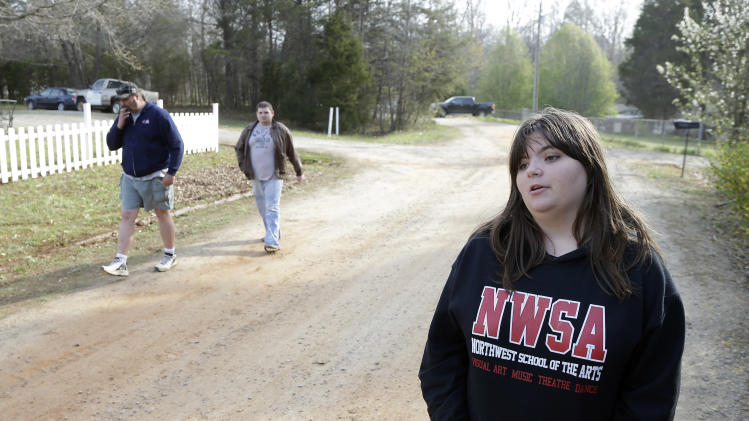 Chelsea Jones, 14, walks away from the scene, Monday, April 8, 2013, where two children she babysat for the past few months died when a wall of dirt fell on them while they were playing in a hole at a construction site behind the children's home, on Sunday, in Stanley, N.C. Following Chelsea away from the scene is her father, Bradley Jones, and brother Bradley Jones Jr. (AP Photo/Bob Leverone)