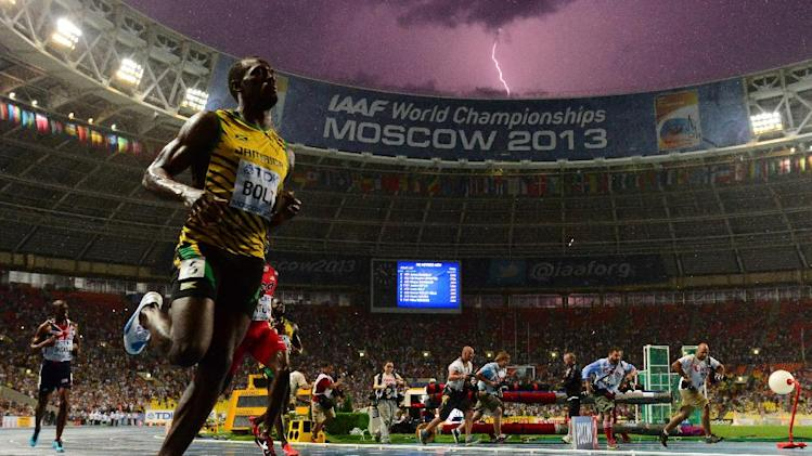 Usain Bolt wins the 100 metres final at the World Championships in Moscow on August 11, 2013 while a lightning strikes in the sky