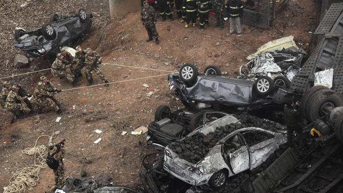 CORRECTS DATE - Chinese paramilitary policemen pull at car wreckage at the accident site where an expressway bridge partially collapsed due to a truck explosion in Mianchi County, Sanmenxia, central China's Henan Province, Friday, Feb. 1, 2013. A truckload of fireworks intended for Lunar New Year celebrations went off Friday in a massive, deadly explosion that destroyed part of an elevated highway in central China, sending vehicles plummeting 30 meters (about 100 feet) to the ground. (AP Photo) CHINA OUT