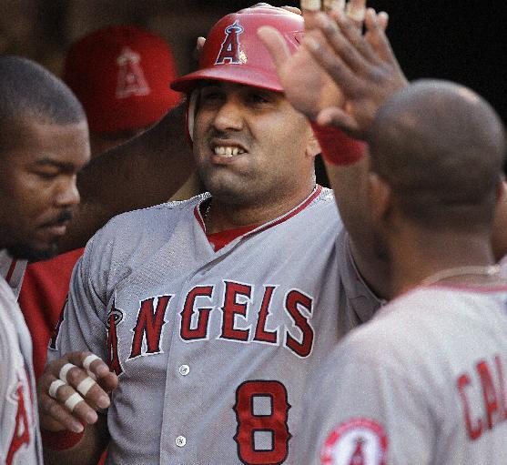 Los Angeles Angels' Kendrys Morales (8) is congratulated after scoring against the Oakland Athletics in the second inning of a baseball game Monday, Aug. 6, 2012, in Oakland, Calif. Morales scored on a single bu Angels' Erick Aybar. (AP Photo/Ben Margot)