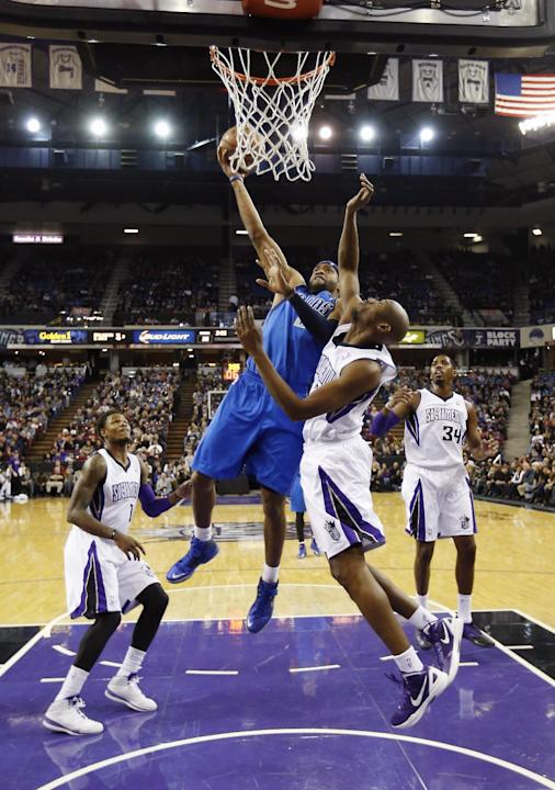 Dallas Mavericks guard Vince Carter, second from left, drives to the basket against Sacramento Kings forward Travis Outlaw, second from right, as Kings' Ben McLemore, left, and Jason Thompson, rig