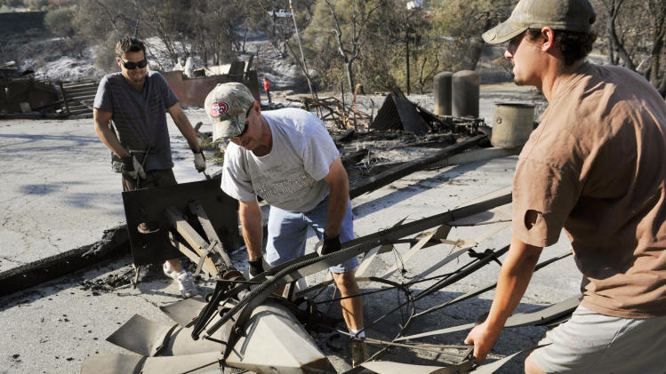 Troy Bratty, center, with the help of Nathan Nott, left, and Corey Andrews, move a charred and fallen windmill which fell on the property at the intersection of Old Barn Way and Highway 41 to a waiting trailer for preservation a day after the Junction fire swept across Highway 41 in Oakhurst, Calif., Tuesday, Aug. 19, 2014. (AP Photo/The Fresno Bee, Eric Paul Zamora)