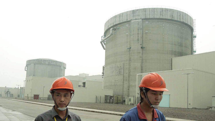 "FILE - In this June 10, 2005 file photo, workers walk past a part of Qinshan No. 2 Nuclear Power Plant, China's first self-designed and self-built national commercial nuclear power plant in Qinshan, about 125 kilometers (about 90 miles) southwest of Shanghai, China.  China is ready to approve new nuclear power plants as part of ambitious plans to reduce reliance on oil and coal, ending a moratorium it imposed because of Japan's Fukushima disaster in 2011.  The Cabinet on Wednesday, Oct. 24, 2012,  passed plans on nuclear power safety and development that said construction of nuclear power plants would resume ""steadily.""  (AP Photo/Eugene Hoshiko, File)"