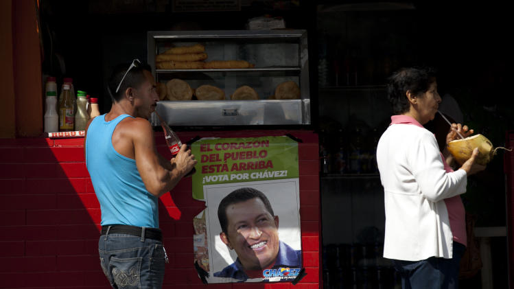 People drink beverages at a food stand where a poster hangs of Venezuela's President Hugo Chavez near the Military Hospital in Caracas, Venezuela, Thursday, Feb. 21, 2013. The government has not released a single photo of Chavez since his return from Cuba on Monday, and that has some Venezuelans doubting whether he's in the military hospital. Others insist he is there, just out of sight while undergoing treatment. Chavez, who has been undergoing cancer treatment in Cuba on and off since June 2011, has said he has had tumors removed from his pelvic region and has undergone chemotherapy and radiation treatment. (AP Photo/Ariana Cubillos)