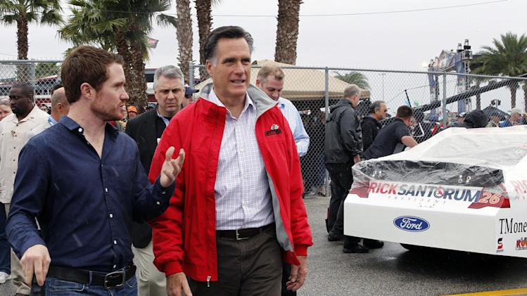 Republican presidential candidate, former Massachusetts Gov. Mitt Romney, right, walks with driver Brian Vickers, left, as they pass a race car sponsored by Romney's rival Rick Santorum before the NASCAR Daytona 500 Sprint Cup series auto race at Daytona International Speedway in Daytona Beach, Fla., Sunday, Feb. 26, 2012. (AP Photo/Terry Renna)