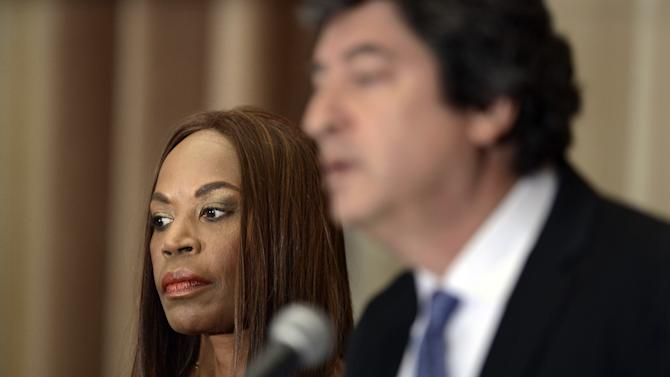 Liz Banks, left, widow of former Chicago Cubs baseball player Ernie Banks, looks on as attorney Mark Bogen speaks to the media during a press conference about the death of the Hall of Famer in Chicago, Sunday, Jan. 25, 2015. Bogen, an attorney for the Banks family, said the Cubs great died of a heart attack. (AP Photo/Paul Beaty)