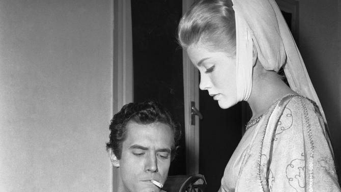 """FILE - In this Dec. 19, 1960 file photo, actress Dolores Hart lights a cigarette for actor Bradford Dillman, in a break of the shooting of the movie, """"Saint Francis of Assisi,"""" in Rome. Dillman had the starring role of Saint Francis, while Hart played the part of Saint Clare, the nun who founded the order of St. Clare. Hart, whose luminous blue eyes entranced Elvis Presley in his first on-screen movie kiss, is now a cloistered nun and praying for a Christmas miracle. She walked away from Hollywood stardom in 1963 to become a nun in rural Bethlehem, Conn. Now she finds herself back in the spotlight, but this time it's all about serving the King of Kings, not smooching the King of Rock and Roll. The former brass factory that houses Mother Dolores and about 40 other nuns cloistered at the Abbey of Regina Laudis in Bethlehem, Conn., needs millions of dollars in renovations to meet fire and safety codes, add an elevator and make handicap accessibility upgrades. (AP Photo/CR, File)"""