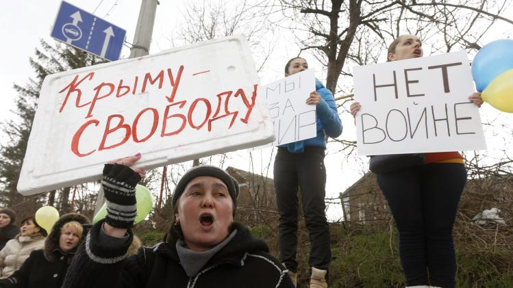 Participants hold placards and shout slogans during an anti-war rally in the Crimean village of Eskisaray, outside Simferopol