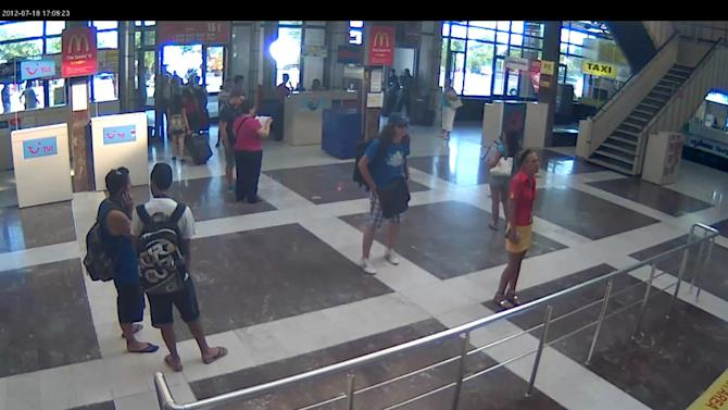 This image taken from CCTV provided by the Bulgarian Interior Ministry who claim it shows the unidentified bomber, centre, with long hair and wearing a baseball cap, at Burgas Airport on Wednesday, July 18, 2012. The brazen daytime bombing that killed seven people and injured dozens on a bus full of Israeli tourists was most likely a suicide attack, Bulgarian officials said Thursday. Israel stood by its claim that Iranian-backed Hezbollah was responsible and vowed to hit back. The identity of the suspected bomber was still unknown but a Michigan driving license that he carried was a fake, Bulgarian Prime Minister Boiko Borisov said. (AP Photo/Bulgarian Interior Ministry)