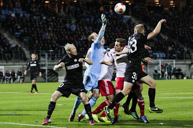 RB Salzburg's goalkeeper Peter Gulacsi, second left, clears the ball between Esbjerg fB's Hans Henrik Andreasen, left, and Jens Berthel Askou, right, during the Europa League group C soccer match, Thu