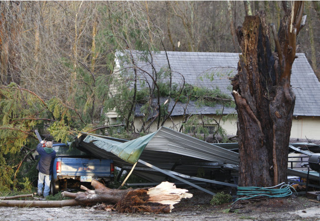 A man cuts trees off his truck after a possible tornado hit the village of Moscow, Ohio, Friday, March 2, 2012. Powerful storms stretching from the Gulf Coast to the Great Lakes flattened buildings in