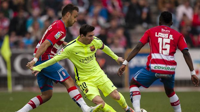 Barcelona's Lionel Messi, center, duels for the ball against Granada's Juan Torres, left, and Lassane Bangoura during a Spanish La Liga soccer match between Granada and FC Barcelona at Los Carmenes stadium in Granada, Spain, Saturday Feb. 28, 2015. (AP Photo/Daniel Tejedor)