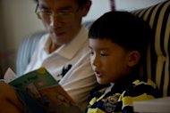 Eight-year-old Zhang Hongwu reads with his father Zhang Qiaofeng during his home schooling at their apartment in Beijing. Giving up his successful career as the head of a medical research firm to spend his days at home reading from children&#39;s story books was a tough choice for Chinese father Zhang Qiaofeng, but in the end, he felt he had no other option