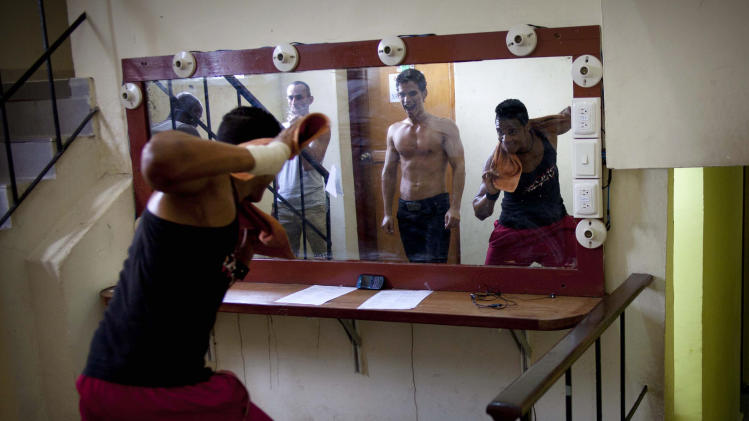 In this May 11, 2013, dancers warm up for their presentation against homophobia at the Karl Marx theater in Havana, Cuba. A week of drag shows, colorful marches and social and cultural events in Havana culminates Friday with celebrations of the International Day Against Homophobia. Gays were persecuted for decades after the 1959 Cuban Revolution, sometimes sent to grueling rural work camps along with others considered socially suspect by the Communist government. But there has been a gradual shift away from macho attitudes, and Fidel Castro himself has publicly regretted the mistreatment of people seen as different. (AP Photo/Ramon Espinosa)