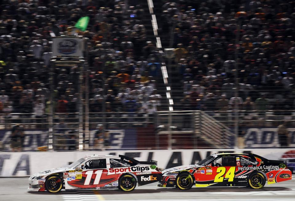 Denny Hamlin (11) gets a push from Jeff Gordon (24) during the final restart in the NASCAR Sprint Cup Series auto race at Atlanta Motor Speedway, Sunday, Sept. 2, 2012, in Hampton, Ga. (AP Photo/Rainier Ehrhardt)