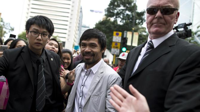 Boxer Manny Pacquiao of the Philippines is escorted by security personnel as he attends a promotional event in Hong Kong
