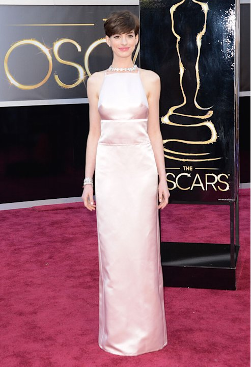 "Does Anne Hathaway know she's at the Oscars? The ""Les Miserables"" actress and Oscar nominee tones it down in a pale pink Prada dress. But even though it's a simple look, the dress in"