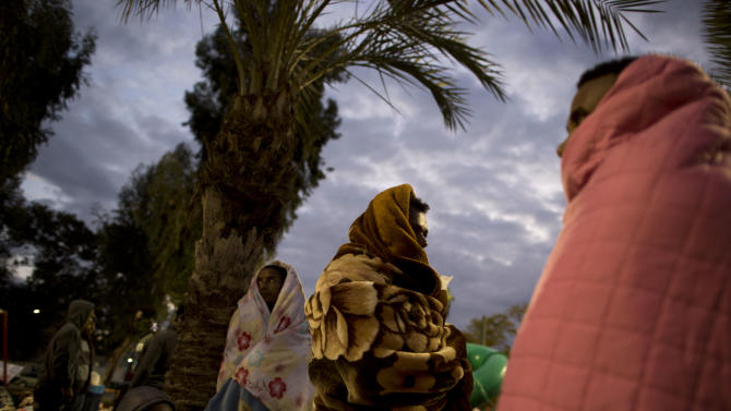 African migrants cover themselves with blankets in a park during a protest demanding asylum and work rights from the Israeli government, in Tel Aviv, Israel, early Tuesday, Feb. 4, 2014. In recent weeks, African migrants, mostly from Eritrea and Sudan, have staged a series of demonstrations demanding they be recognized as refugees, a status that would give them residency rights. Israel sees many of them as economic migrants and has tried a number of tactics to stop the migrants' influx or keep their numbers down. It has built a fence along the border with Egypt, passed a law that allows for the migrants' detention and offered financial incentives to urge them to leave. (AP Photo/Oded Balilty)