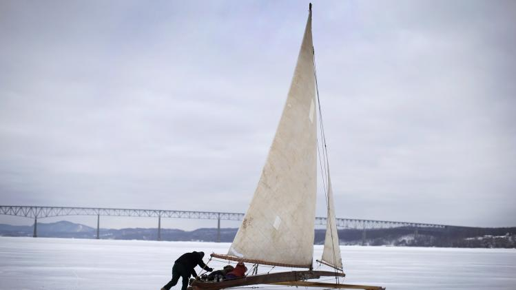 Reid Bielenberg from Athens, New York, steers his antique ice sailing boat with passengers out onto the frozen Hudson River near, Astor Point in Barrytown, New York