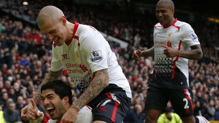 Liverpool's Suarez celebrates with Skrtel and Johnson after scoring his sides third goal during their English Premier League soccer match against Manchester United at Old Trafford in Manchester
