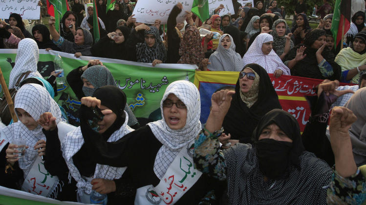 "Pakistani Shiite Muslim women chant anti U.S. slogans during a demonstration that is part of widespread anger across the Muslim world about a film ridiculing Islam's Prophet Muhammad, Sunday, Sept. 23, 2012 in Lahore, Pakistan. The woman, center, wear a banner that reads, ""at your service Hussein."" (AP Photo/K.M. Chaudary)"