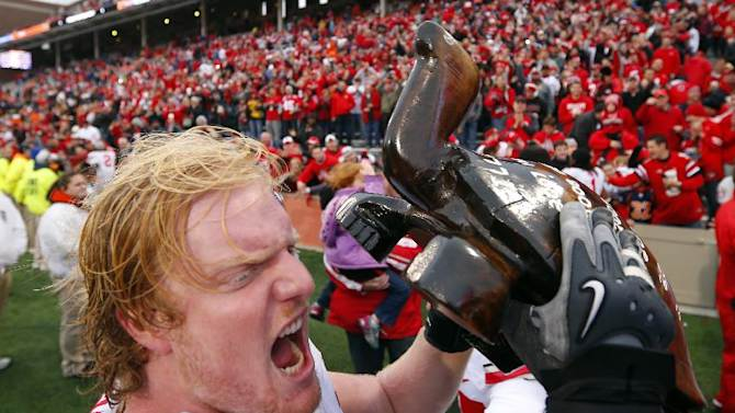 Ohio State offensive linesman Jack Mewhort (74) celebrates with the wooden turtle trophy named Illibuck after beating Illinois during an NCAA college football game on Saturday, Nov. 16, 2013, in Champaign, Ill. Ohio State won the game 60-35. Illibuck is a carved wooden turtle that serves as the trophy awarded to the winner of the game since 1925. (AP Photo/Jeff Haynes)
