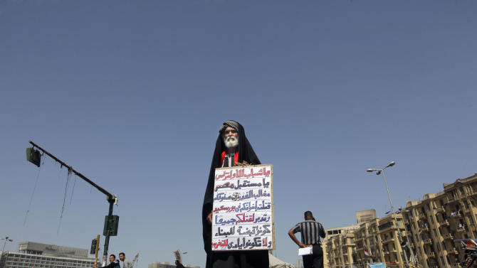 """Mohammed Atian, 60, who is referred to by protesters as the father of revolutionaries, stands in Tahrir Square, the focal point of the Egyptian revolution, in Cairo, Egypt, Monday, March 11, 2013. Atian is holding a sign with a message to the Ultras Ahlawy, that supports the Cairo-based Egyptian premier league soccer club Al-Ahly. The Arabic reads, """" To Ultras youth: you are the future of Egypt, claws of treachery have killed your brothers in Port Said and dispersed your lines and are planning to kill all of you, be a grip for building and not for devastation."""" (AP Photo/Amr Nabil)"""