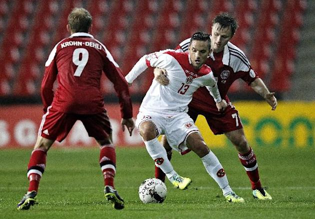 Malta's Andre Schembri, center, is challenged by Denmark's Michael Krohn-Dehli, left, and William Kvist during their group B World Cup qualifying soccer match in Parken, Copenhagen, Tuesday Oct. 15, 2