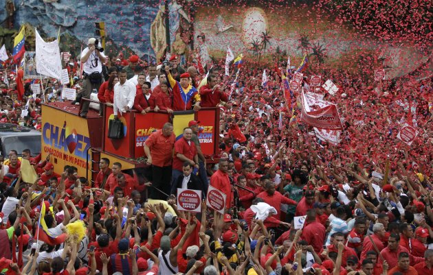 Venezuela's President Hugo Chavez waves to the crowd while riding atop a truck upon his arrival to the elections office in Caracas, Venezuela, Monday, June 11, 2012. Chavez rallied thousands of his su