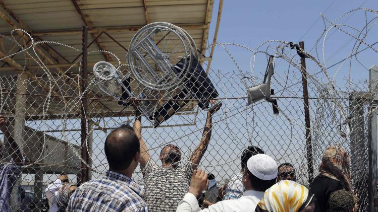 Palestinian man carries a wheelchair to be passed over a fence to others trying to cross into Egypt, at Rafah border crossing in the southern Gaza Strip