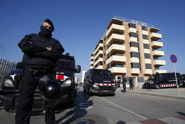 "Police officers stand guard in front of a building owned by national ""bad bank"" Sareb, which had been occupied by squatters after the eviction of its residents in Salt"