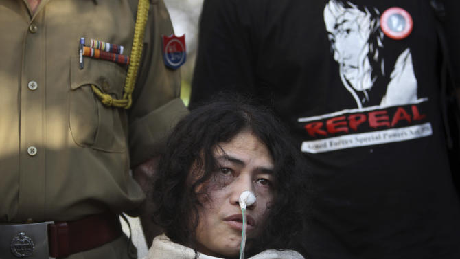 An Indian policeman, left and a supporter stand behind Irom Sharmila, who has been on a hunger strike for 12 years to protest an Indian law that suspends many human rights protections in areas of conflict, speaks during a press conference, in New Delhi, India, Monday, March 4, 2013. Sharmila who has been force fed through a tube by authorities was charged Monday with attempted suicide in a case likely to bring major attention to her quiet protest in the tiny northeastern state of Manipur against the Armed Forces Special Powers Act. (AP Photo/Tsering Topgyal)