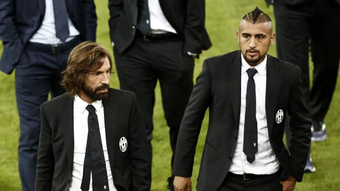 Juventus' Vidal and Pirlo leave the pitch after a team visit at Karaiskaki stadium on the eve of their Champions League soccer match against Olympiakos in Piraeus near Athens