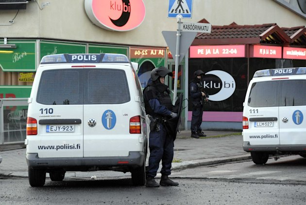 Police officers guard the area in Hyvinkaa, Finland, where a gunman has killed one person and wounded eight others in what appeared to be a random shooting, police said Saturday May 26, 2012. (AP Phot